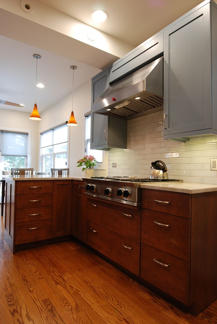 2-tone transitional kitchen, pendant lighting over island, blue painted cabinetry, peninsula, Blue Star range top, stainless steel canopy hood, subway tile backsplash, warming drawers