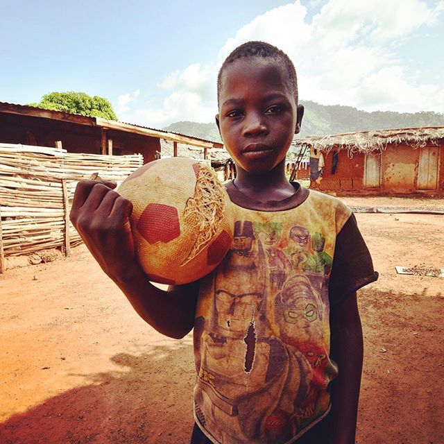 A young boy learning to play football poses with his ball in the village of Diebly, at the foot of Mont Peko. ⚽️ #football #beautifulgame #simplepleasures #ball #friends #love #photooftheday #cotedivoire