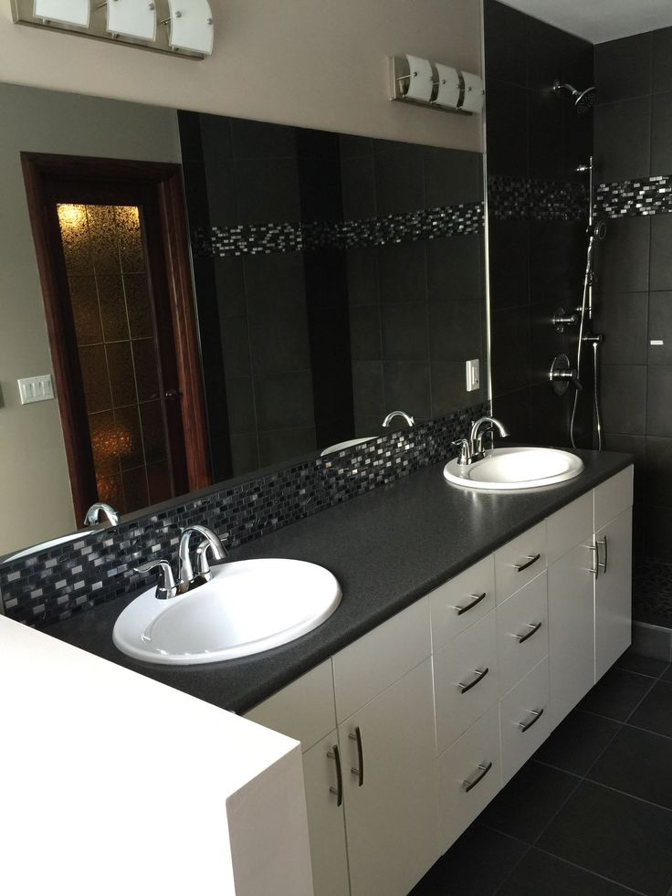On this renovation we installed a new vanity, vanity top, sinks and faucets, tiled shower, shower head and slide bar, tile floor with infloor heat and low flush toilet.