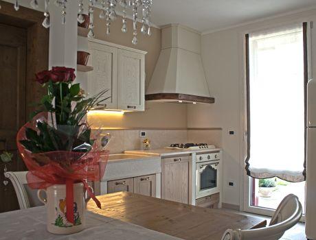Cucina realizzata con finitura bicolor panna e castagno naturale, piano e alzata in marmo botticino.