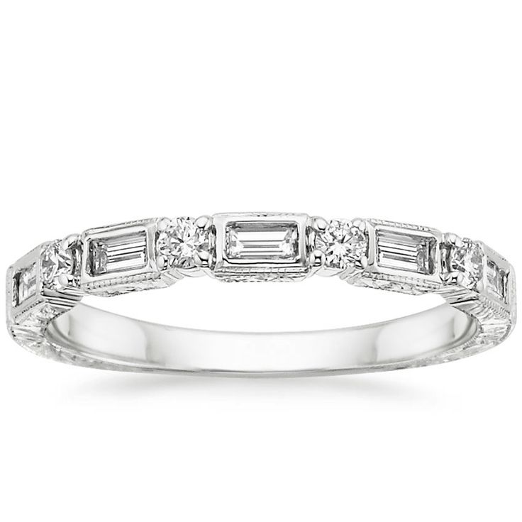 Evocative of days gone by, this vintage inspired ring features sparkling diamond baguettes alternating with round diamonds and surrounded by delicate milgrain on the top half of the shank. The band is hand-engraved in a fanciful floral pattern on both the top and sides for additional appeal.