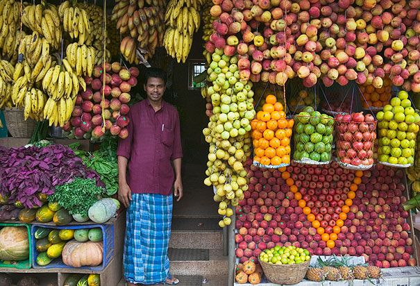 A VENDOR STANDS AMONG FRUITS AND VEGETABLES AT AN OUTDOOR MARKET IN KERALA, INDIA
