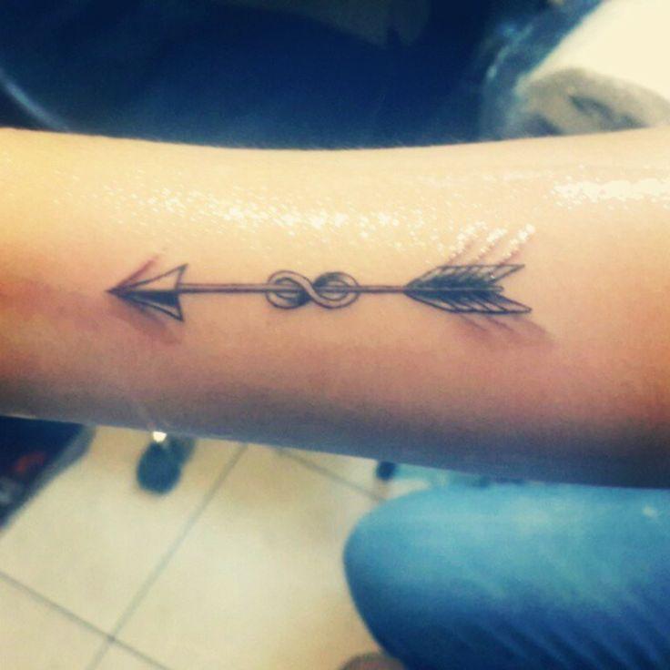 Pequeño tatuaje de una flecha cruzando el símbolo infinito en el antebrazo de…