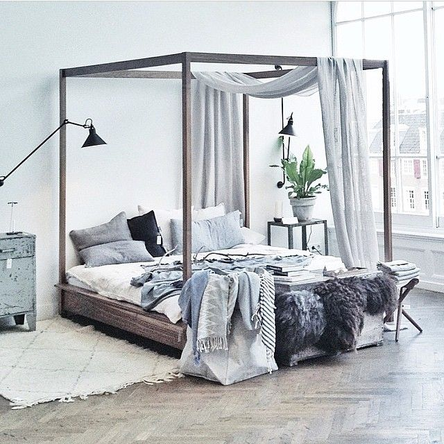 King Sized Four Poster bed love the rare breed sheepskins hung over end.