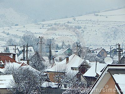Snowy houses with mountains in the background, photographed outdoors at winter in Romania.
