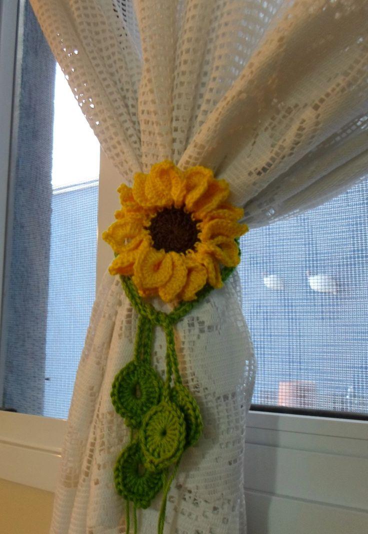 Prendedor de cortina feito em crochê, motivo girassol de 9 cm. <br>O prendedor possui dois cordões de correntinhas (0,85 e 0,75 cm) de crochê para dar um charme a sua cortina. Faço os cordões no tamanho desejado. Consulte o laboratório <br>Valor corresponde à unidade e não ao par.