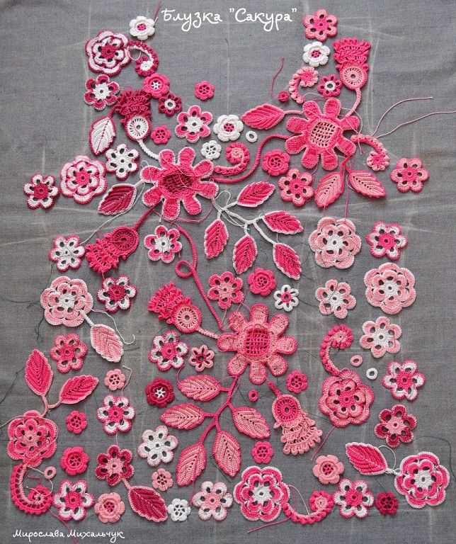Pink Irish crochet flowers and leaves laid out in preparation for the connecting crochet work
