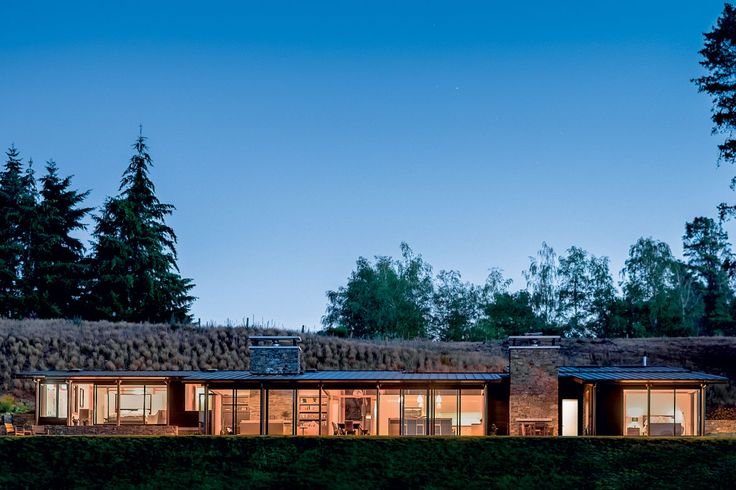 Large schist fireplaces counter the expansive glazing, visually anchoring the house to the land and imparting a sense of permanence.