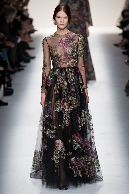 Look 65, Valentino Fall 2014. One of many variations on a theme: wondrous garden-of-eden motif on transparent tulle, with a simple silhouette: high neck, long sleeves, shirt waist with dirndl skirt. So, they're taking the simple and making it extraordinary!