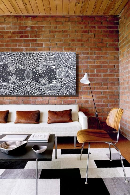 Tanya Bird Mpetyane's piece looks so comfortable hung up against this exposed brick wall. For a room that's bursting with earthy and wooden tones, choose black and white pieces that won't disrupt the existing colour scheme.