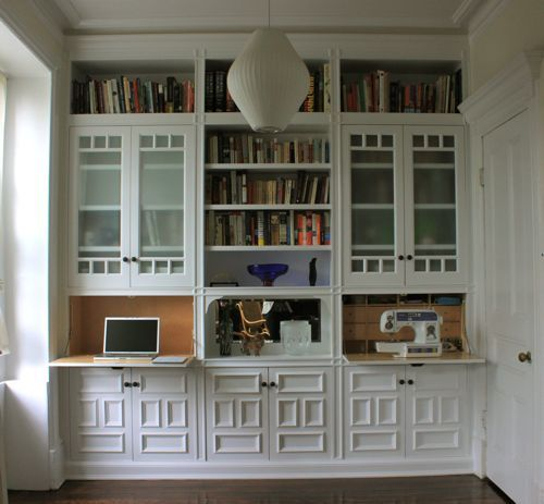Phase 1 and/or Final: this is waaaaaay too fussy design-wise, but shows built-in with drop-front desk. Combination of open shelves and concealed shelves and cupboards. Just lose the fuss!!!