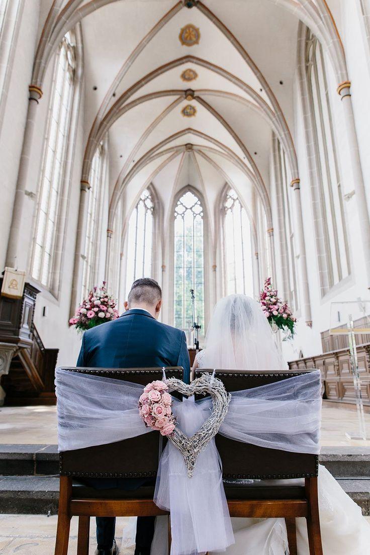 Die Stühle von Braut und Bräutigam in der Kirche mit Tüll zusammen gebunden u…