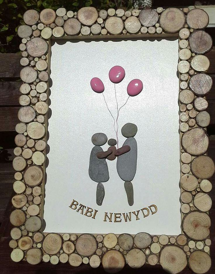 New baby girl pebble picture in Welsh, framed with wood slices.