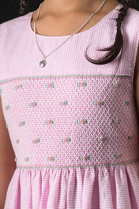 Hand smocked, hand embroidered, and expertly sewn by disadvantaged women at a self help center in Thailand. Princess Charming® pink striped seersucker dress details: Self piping around neck and armholes, white buttons down the bodice back, long wide ties for making a bow and adjusting size. Smocking is self lined. Blindstitched hem has ample material for lengthening. Dress pictured with heart necklace also from Kasumisou Gallery.