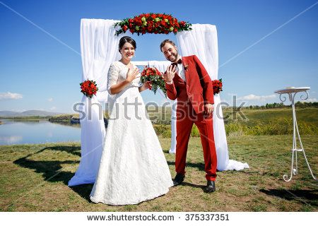 Just married positive bride and groom show rings after the wedding ceremony on background of arch with red flowers and white cloth, outdoors, on banks of the river. Marsala color and decoration style.