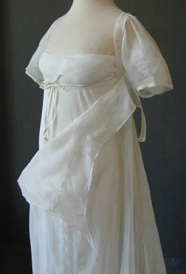 """White muslin wedding dress (showing fall-front bodice construction and underdress), English, c. 1805-11. There is a hand written note in ink with this item: """"India muslin wedding dress with neckline insertion, worn by my grandmother Hon Jane Elizabeth Wain?, daughter of Lord Headley of Agador, Co Kerry (Ireland) 1811. Lived at Lea Castle, Simmonsbath, Exmoor. Died in Rome."""" It also says """"Wolverley House, Jersey."""" They probably had two residences."""