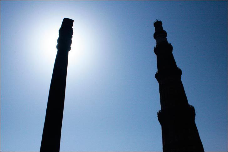 The Sun shines behind the Iron Pillar with the Qutub Minar on the right