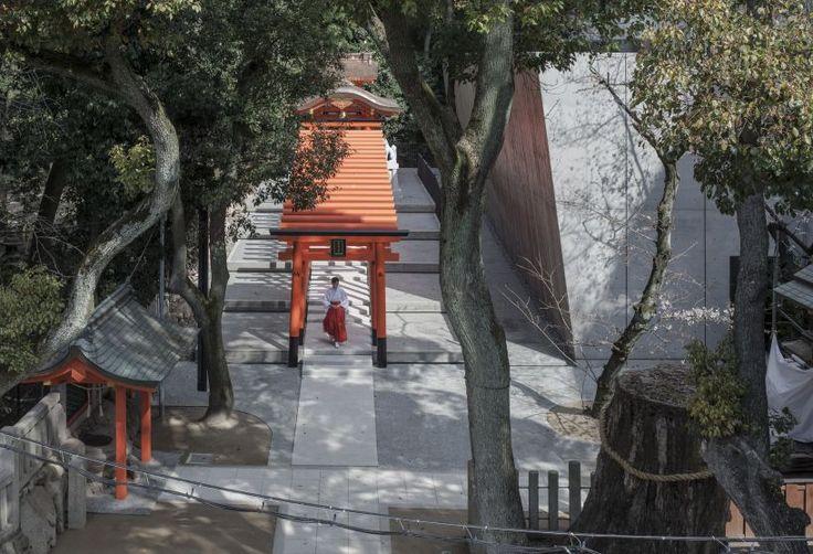 the takenaka group has installed a slanted concrete volume and wooden inari shrine at the ikuta shrine in kobe city, japan.