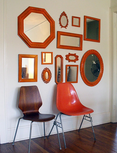 find odd shaped mirrors, paint the frames the same color and arrange on a wall.