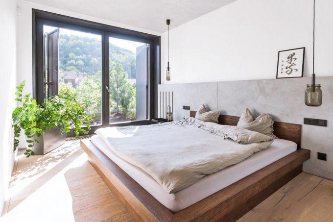 Jednoduchá ložnice zcela kopíruje charakteristické rysy celé realizace – převládá dřevo, beton a velké bílé plochy. Dovoluje tak vyniknout působivému výhledu do zeleně