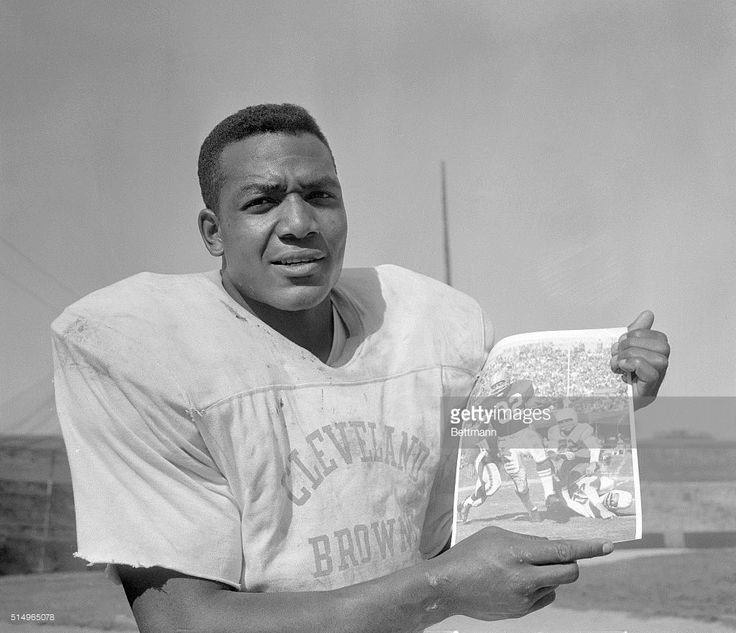 Jim Brown, Cleveland Browns' fullback, holds up a UPI photo of himself in action against the Chicago Cardinals October 12. Brown has picked up 482 yards in three games, 202 more yards than Tom Wilson of the Los Angeles Rams, who is second in the rushing department in the NFL. Brown also leads the NFL in scoring with eight touchdowns and 48 points.