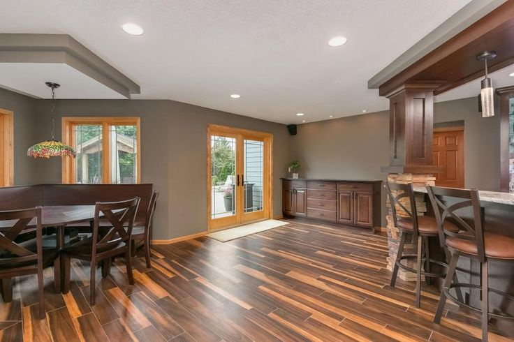 A stunning, unique wood floor wows in this basement space. An additional table and seating area and bar create an ideal space for entertaining, hosting game nights and escaping the hustle and bustle in your own home.