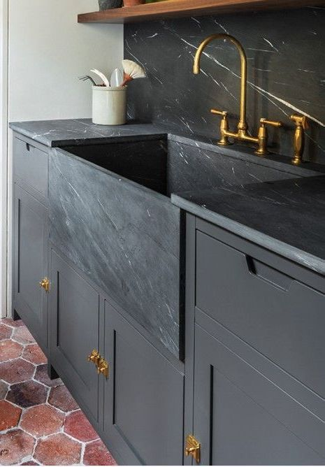 Dark cabinets with huge soapstone sink.