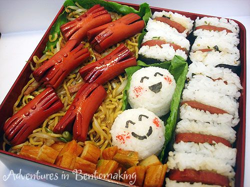 Bento for the zoo with spam musubi, onigiri, fishcake, yakisoba, and crab hotdogs.