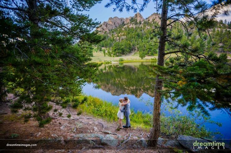 A bride and groom embrace on the shore of Lily Lake, Colorado