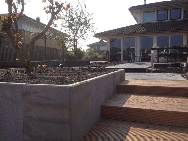 Tuinaanleg, meerdere niveau's. Schellevis tegels, hardhouten vlonders, cortenstaal, grondkeringen.