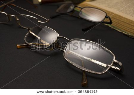 Eyeglasses with magnifying glass on dark surface with books. High resolution image design for Ophthalmologist concept. - stock photo