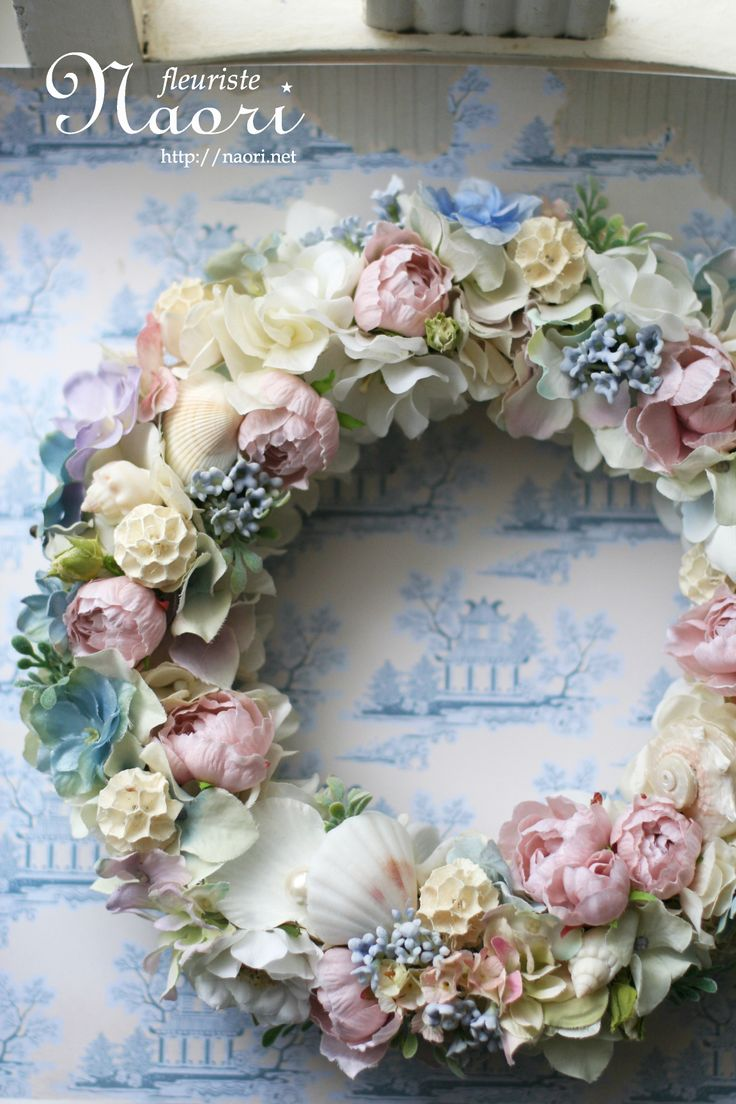 Sea shell/beach wreath. Bright pastel flowers and white sea shells. I'd LOVE some glass pebbles in this arrangement.