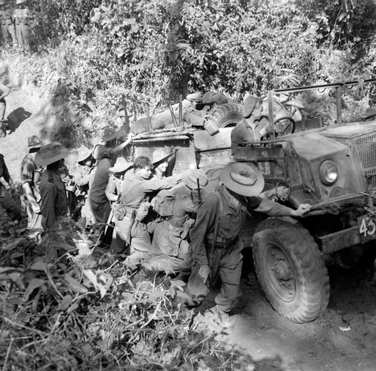 Men of the 36th Infantry Division push a CMP truck up a muddy slope on the road to Mandalay, February 1945.