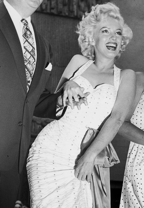 Marilyn Monroe during the imprinting of her shoe in wet cement at Grauman's Chinese Theatre on June 26, 1953