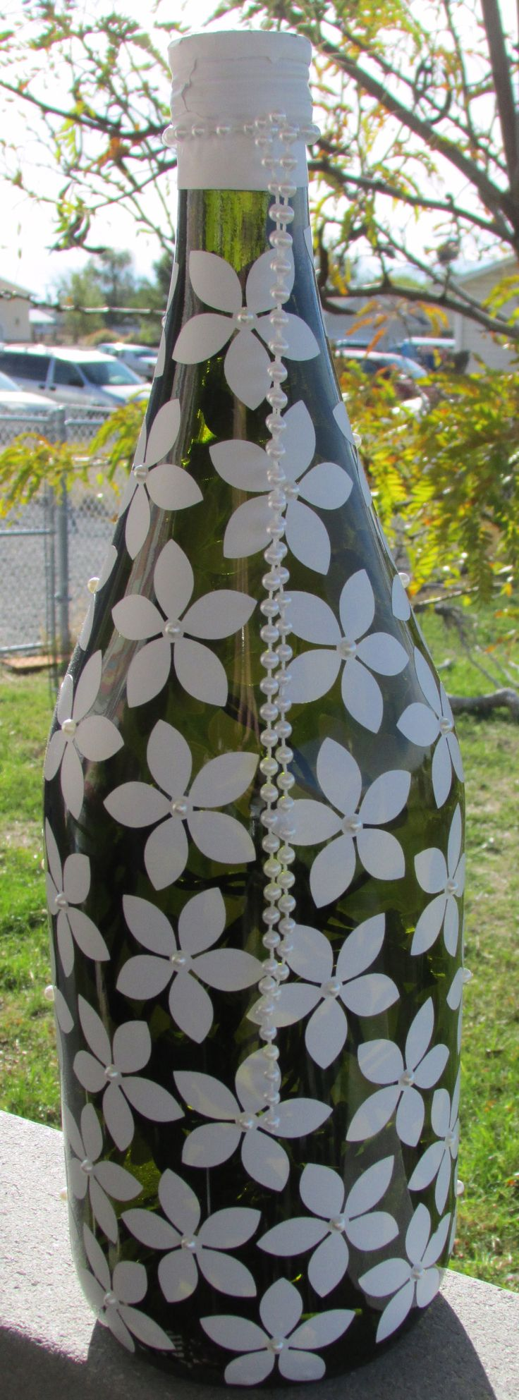Saw a bottled painted similar to this. This is one flower shape out of vinyl with pearl centers. There are about 70 flowers on the bottle. Created by Karen Bennett