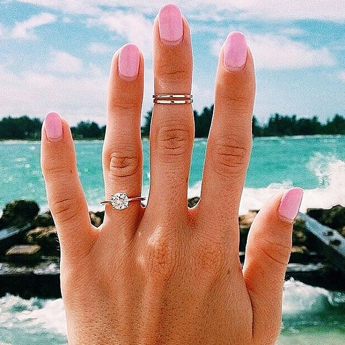 An engagement ring is worn with silver midi rings