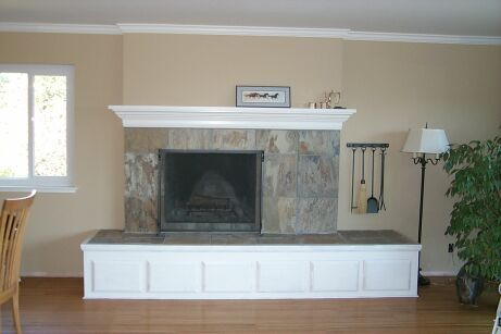 custom drawers built under the cantilevered hearth with matching custom mantle. The brick was faced in natural slate in a neutral but interesting color, and the mass was reduced by using textured sheetrock above the mantle to match the existing walls.