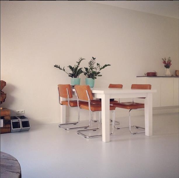Home sweet home. Combinatie van strakke witte meubels op lichtgrijze gietvloer met warme accenten. Industriële look.