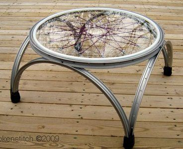 hand cut reclaimed window glass edged in flexible plastic inside of sectioned bicycle rims with nonskid feet made from an inner tube