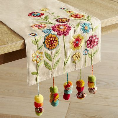 Something to cheer about: Our brightly colored table runner with embroidered and appliqued flowers, corded tassels and sprightly pompoms.