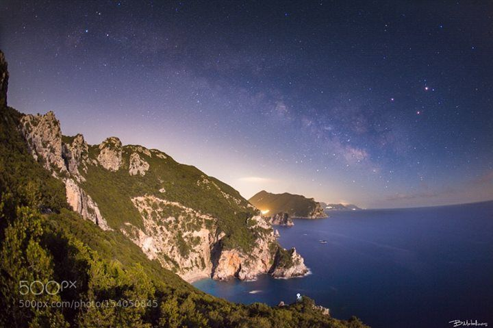 """Nightscape above Ermones  Nightscape above Ermones  Night landscape in a green hillside near Ermones in western Corfu. The Milky Way shins in the firmament while on the right the planets Saturn and Mars with Antares little lower are forming a """"red triangle"""" at the top of Scorpio the Scorpion. While to the upper ad left of the image the huge star Deneb just about 2000 light years awy shines on the tail of Cygnus the Swan. Lower on the image we can see formations of sandstones and marls of…"""