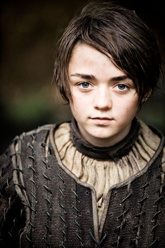 Arya Stark is a major character in the first and second seasons. She is played by starring cast member Maisie Williams and debuts in the series premiere. Arya is a daughter of House Stark who has been separated from her family. She is fiercely independent and is often mistaken for a boy. She wields a sword named Needle, a gift from her half-brother Jon Snow, and has been trained in the Braavosi style of swordfighting. She adopted the direwolf Nymeria but they have since been separated.