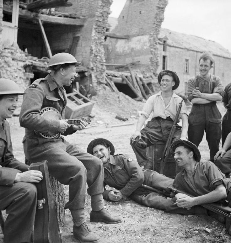 George Formby entertains troops in the ruins of a village in Normandy during an ENSA [Entertainments National Service Association] tour, 30 July 1944.