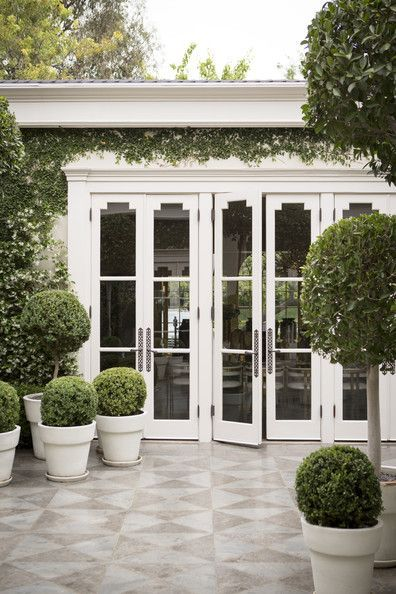 Boxwoods in white planters in Kelly Wearstler's courtyard