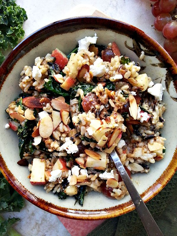 Kale and wild rice bowl with grapes, almonds, apple, and feta tossed in a toasted almond vinaigrette
