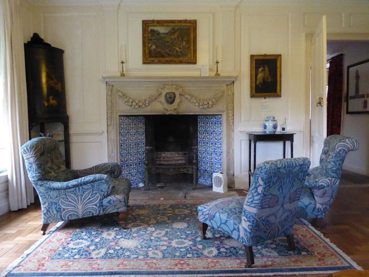 William Morris's country house in the Cotswolds - Turlish tiles around the fireplace and blue chairs in the white panelled sitting room at Kelmscott Manor, Kelmscott, Lechlade, Gloucestershire