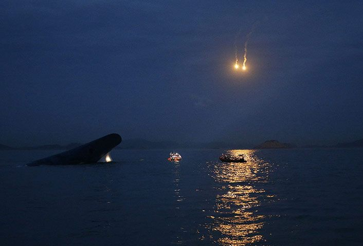 The South Korean ferry 'Sewol' is seen sinking as flares are set off to aid the night search