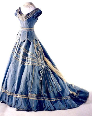"""""""Showcased is a stunning blue silk faille evening gown with a bodice, trained skirt, and separate peplum. This exquisite dress is abundantly decorated with yards upon yards of white silk braid and white and blue silk ribbon.""""  c. 1867"""