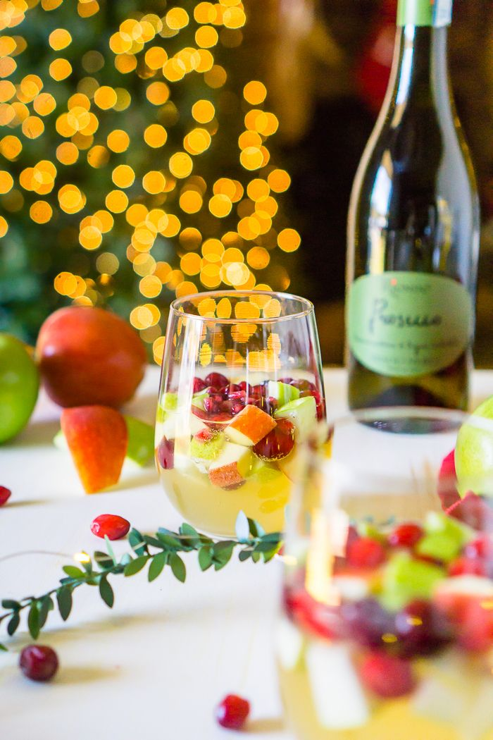I'm dreaming of a White Christmas Sangria, filled with tasty red and green fruit for a festive holiday cocktail! Fill up the sangria pitcher with red and green apples, pears, cranberries and pomegranates, and some white wine and Prosecco, too, of course, for a sparkling sangria! Lightly sweet with tangy fruit makes a Christmas Sangria Recipe your guests will love! | The Love Nerds #Sponsored by @RiondoProsecco #RiondoProsecco #ItalianforHoliday #Prosecco via @lovenerdmaggie
