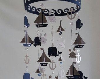 Cette adorable Pirate Ship nautique voilier Mobile aura fière allure dans la chambre de tout petit garçon. (couleurs personnalisées disponibles)  VOUS SOUHAITEZ PERSONNALISER??? Commandez ce mobile et laisser vos sélections de couleurs dans les notes à la Caisse !   ** Bague est 12 rond recouvert de corde comme matériau ** 7 brins de double faces designs, bateaux de pirates, baleines, ancres, helms ** Se bloque à environ 13 de l'anneau à la conception de bas ** agrémenté de perles de verre…